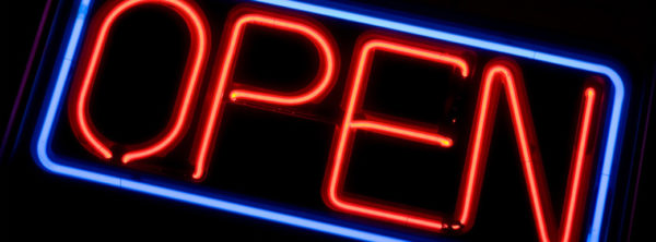 A neon OPEN sign glowing red in the window of a store